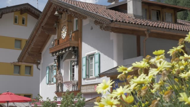 view of ornate house with clock bells in canazei, fassa valley, province of trento, south tyrol, italian dolomites, italy, europe - canazei video stock e b–roll