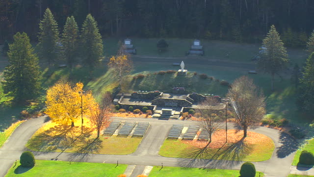 ms aerial view of our lady of grace statue surrounded by autumn color trees / new hampshire, united states - weibliche figur stock-videos und b-roll-filmmaterial
