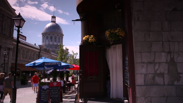 view of outside tables at café in old montreal street with silver domed march bonsecours in background - モントリオール旧市街点の映像素材/bロール
