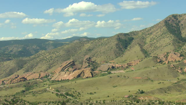 ms ds zi aerial view of outskirts of denver at red rocks mountain park and mountain foothills with bright sky and few clouds / denver, colorado, united states - red rocks stock videos & royalty-free footage