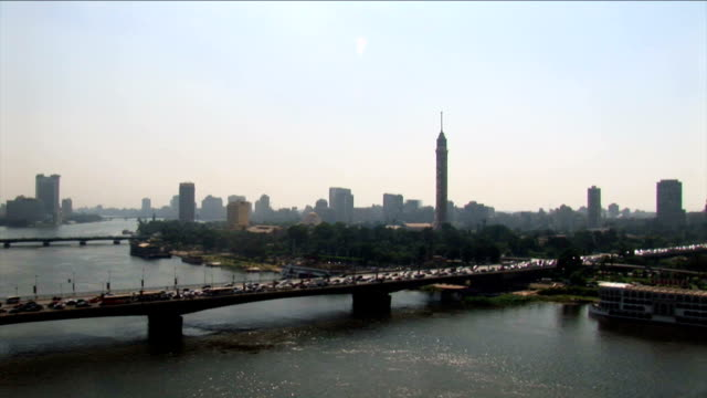 AERIAL WS view of Overlooking city and cars passing on Nile river bridge / Cairo