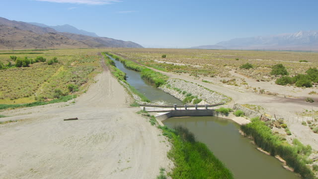 WS AERIAL POV View of Owens River with Los Angeles Aqueduct junction in desert valley, Inyo Mountain of Sierra Nevada in background / California, United States