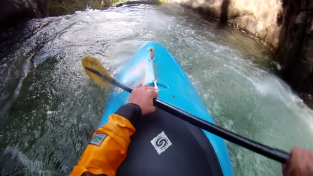 POV view of paddler descending turbulent mtn river