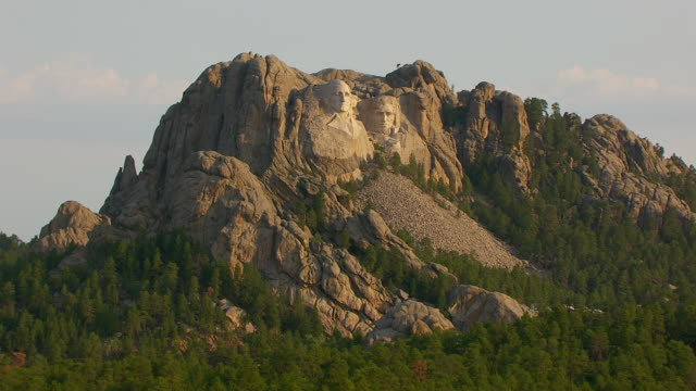 ws aerial ts zi view of pan up from trees and push to faces of george washington and thomas jefferson and theodore roosevelt and abraham lincoln at mount rushmore in pennington county / south dakota, united states - george washington stock-videos und b-roll-filmmaterial