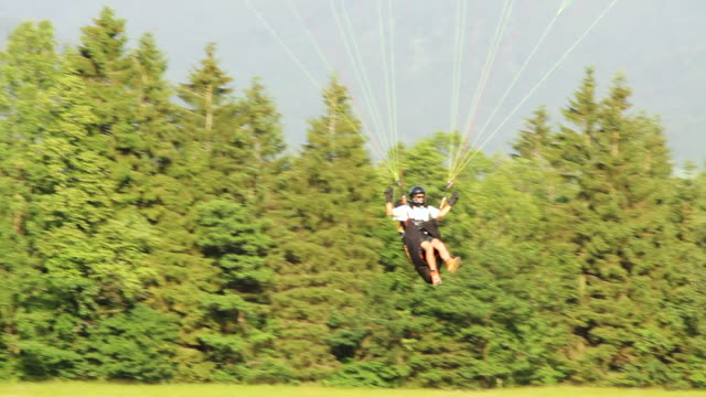 ms pan view of para glider landing on meadow / lenggries, bavaria, germany  - paragliding stock videos & royalty-free footage