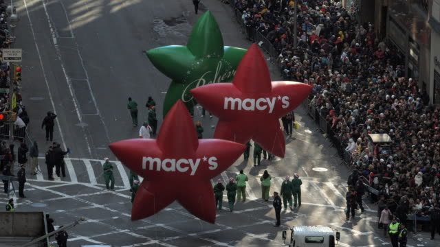 WS View of parade with three inflatable star shape and Macys logo / New York City, New York, USA.