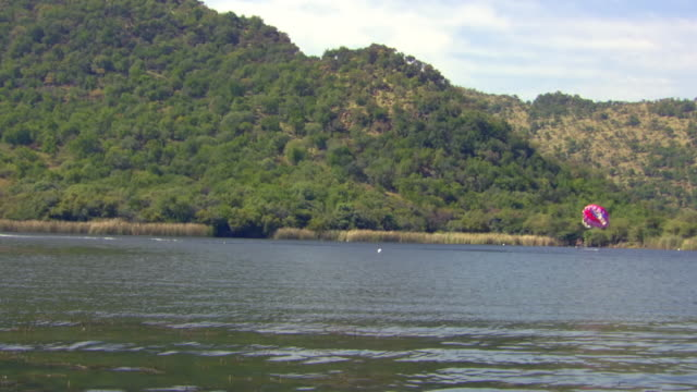 WS TS ZI SLO MO View of Paraglider being pulling behind speed boat and Sun City Dam / North West Province, South Africa