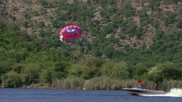 MS TS SLO MO View of Paraglider being pulling behind speed boat, Sun City Dam / North West Province, South Africa