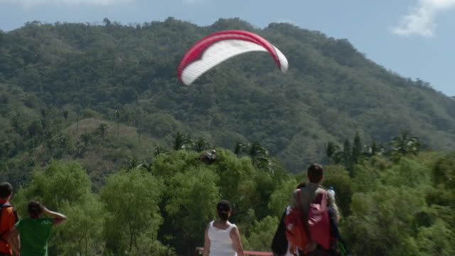 vídeos de stock e filmes b-roll de ws ts zo view of paraglider landing near beach and people watching / yelapa, jalisco, mexico - parapente