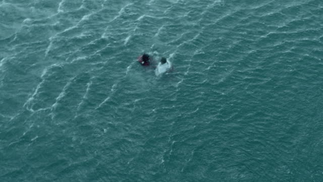 ws aerial ds view of paramedic rescuing man in sea / cape town, western cape, south africa - retter rettungsaktion stock-videos und b-roll-filmmaterial