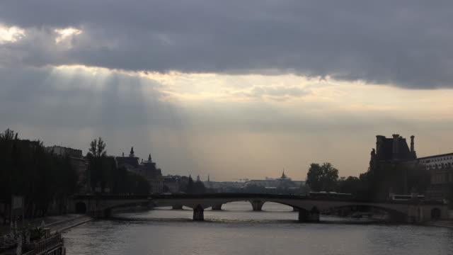 view of paris, bridge over the seine, against the light - ドラマチックな空模様点の映像素材/bロール