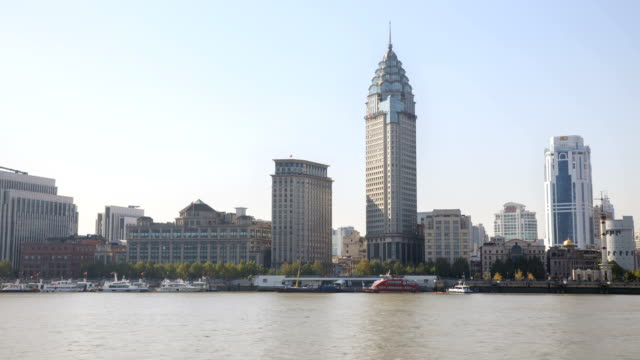 view of passenger terminal and guangming hotel with buildings on the river at daytime in shanghai, china - フェリーターミナル点の映像素材/bロール