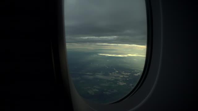 vidéos et rushes de vue des nuages de passage d'une fenêtre d'avion - austria