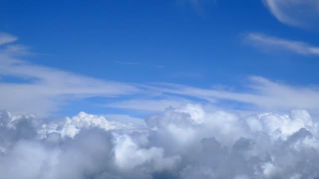 Blick auf den vorüberziehenden Wolken aus einem Flugzeug-Fenster