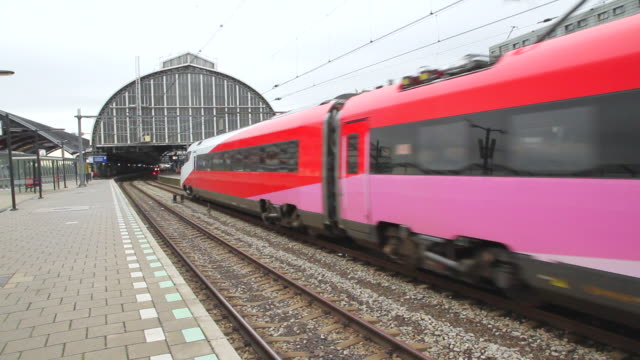 ws view of passing train at amsterdam central train station / copenhagen, denmark - railway station stock videos & royalty-free footage