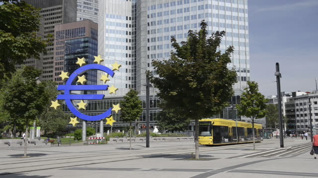 WS View of passing tram in front of euro sign at European Central Bank with moving people / Frankfurt am Main, Hesse, Germany