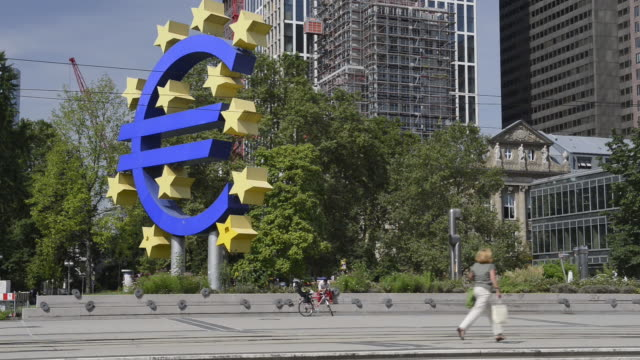 ws view of passing tram in front of euro sign at european central bank with moving people / frankfurt am main, hesse, germany - euro symbol stock videos and b-roll footage