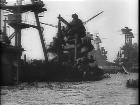 View of Pearl harbor / pan of battleships USS West Virginia USS Maryland and USS Tennessee in harbor / battleship guns just above the water line /...