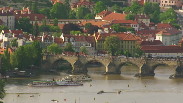 WS AERIAL View of pedestrian crossing bridge and ferry passing down bridge / Prague, Czech Republic