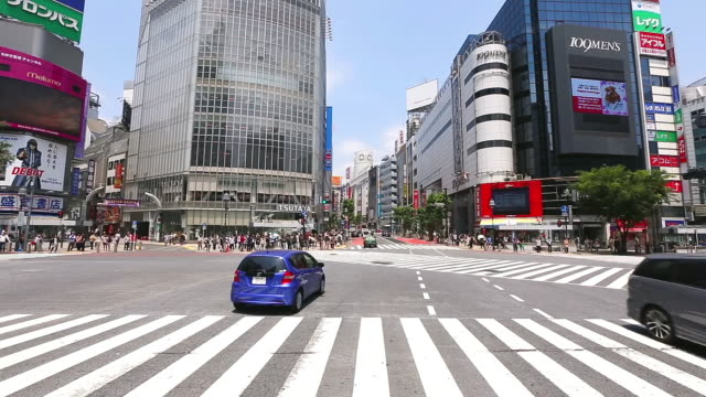 ws pan t/l view of pedestrians and cars crossing at shibuya crossing / shibuya ku, tokyo, japan - 横位置点の映像素材/bロール