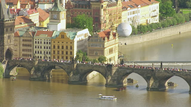 WS AERIAL PAN View of pedestrians walking on bridge over river to air balloon over church / Prague, Czech Republic