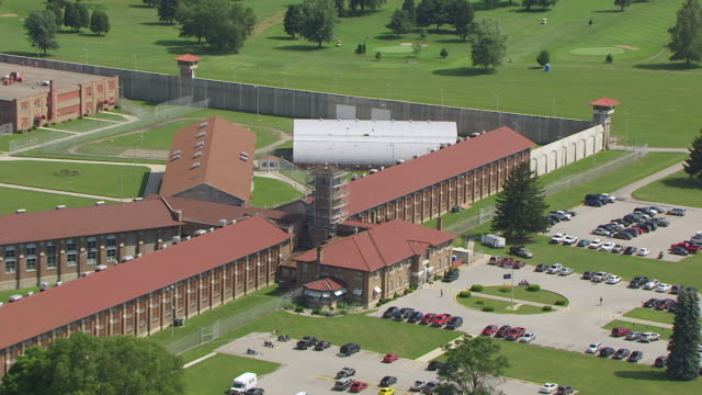 ws zo aerial pov view of pendleton correctional facility with american flag waving in foreground / fall creek township, madison county, indiana, united states - prison building stock videos & royalty-free footage