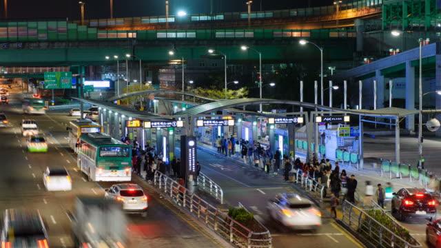 ws t/l view of people and bus stop at suwon station at night / suwon, gyeonggi do, south korea  - suwon stock videos and b-roll footage