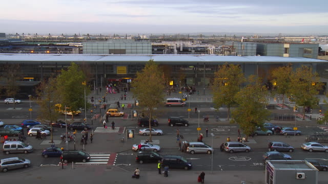 WS T/L View of People and cars moving through drop off point at Heathrow airport / London, United Kingdom