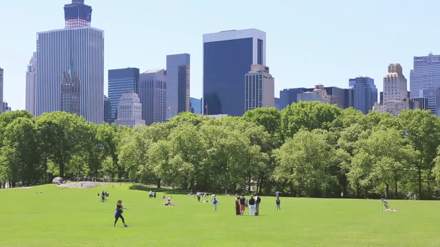 WS PAN View of People and fresh green trees and Manhattan Skyscraper from Sheep Meadow Central Park / New York, United States