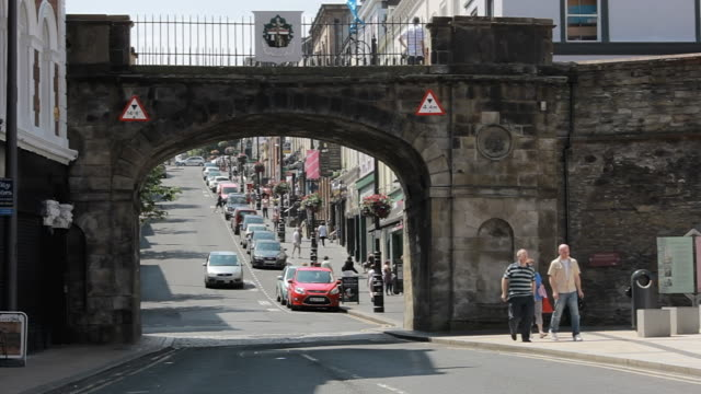 ws view of people at street with old city gate in back / derry, northern ireland, united kingdom  - デリー点の映像素材/bロール