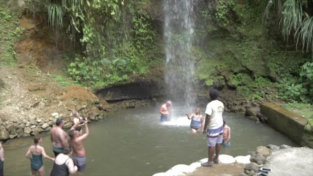 view of people bathing in toraille waterfall, st. lucia, windward islands, west indies caribbean, central america - st lucia stock videos & royalty-free footage