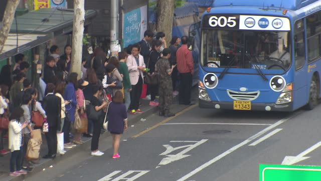 view of people boarding bus at bus stop in yeoungdeungpo area - バス停留所点の映像素材/bロール