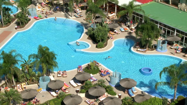 ws view of people by swimming pool at hotel in torremolinos / costa del sol, andalusia, spain - freibad stock-videos und b-roll-filmmaterial