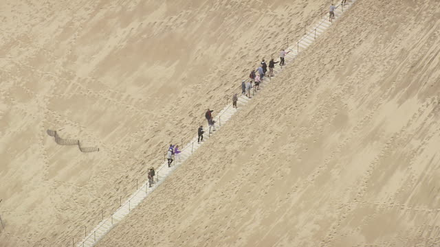 ws aerial pan view of people climbing stairs dune du pilat / aquitaine, france - dune of pilat stock videos and b-roll footage