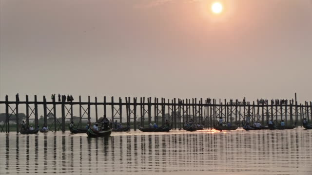 ws view of people crossing a bridge and several boats in the water in front of the bridge  / mandalay, mandalay division, myanmar - mandalay stock videos and b-roll footage