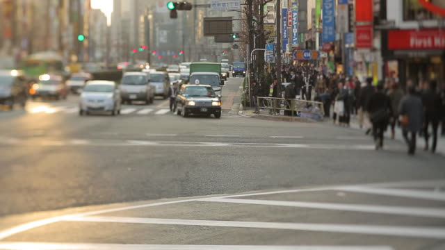 WS PAN View of people crossing busy street with vehicles passing on road in city / Shinjuku, Tokyo, Japan