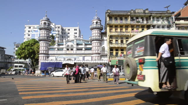 WS View of People crossing street and buses drive at Bengali Sunni Jamae mosque / Yangon, Yangon Division, Myanmar