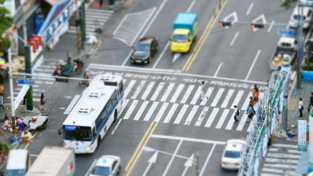 vídeos de stock e filmes b-roll de ms ha t/l view of people crossing  street at  crosswalk and cars driving around gwangjang market in seoul / seoul, south korea - 2013