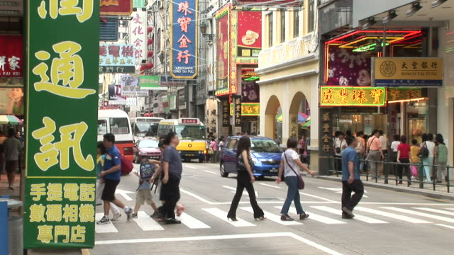 view of people crossing the road in macau china - zebramuster stock-videos und b-roll-filmmaterial
