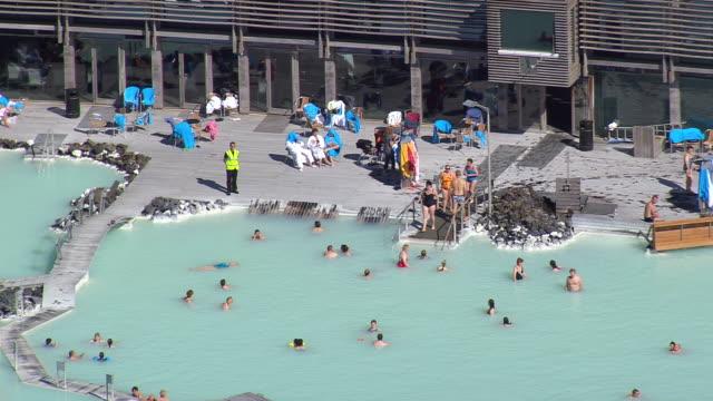 stockvideo's en b-roll-footage met ms aerial view of people enjoying at blue lagoon / iceland - buitenbad