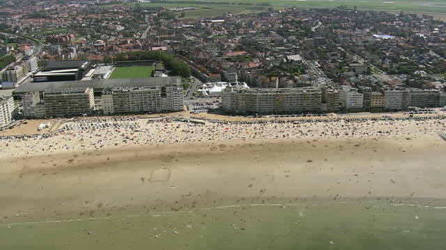 ws aerial pan view of people enjoying at ostende beach / flanders, belgium - kustlinje bildbanksvideor och videomaterial från bakom kulisserna