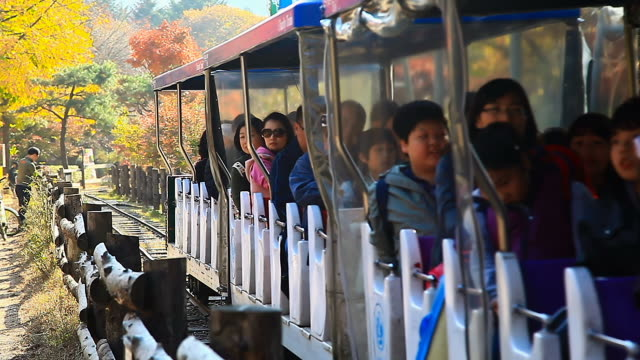 ms view of people going on sightseeing train with smile in nami island / chuncheon, gangwondo, south korea - bahnreisender stock-videos und b-roll-filmmaterial