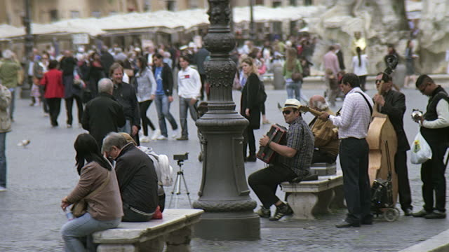 ms view of people moving and musician playing instruments at plaza navona and st agnese in agone / rome, italy - courtyard stock videos & royalty-free footage