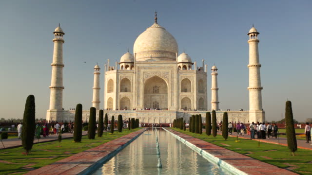 ws view of people moving in front of taj mahal, white domed marble mausoleum and reflecting in pool / agra, uttar pradesh, india - taj mahal stock videos and b-roll footage