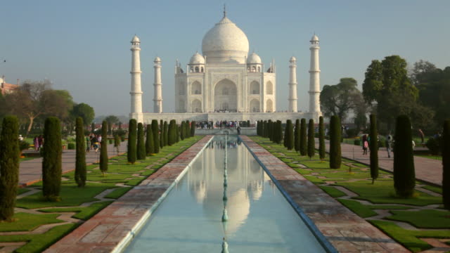 ws view of people moving in front of taj mahal, white domed marble mausoleum and reflecting in pool / agra, uttar pradesh, india - gruppo medio di animali video stock e b–roll