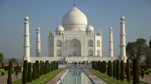 ws t/l view of people moving in front of taj mahal, white domed marble mausoleum and reflecting in pool / agra, uttar pradesh, india - agra stock videos and b-roll footage