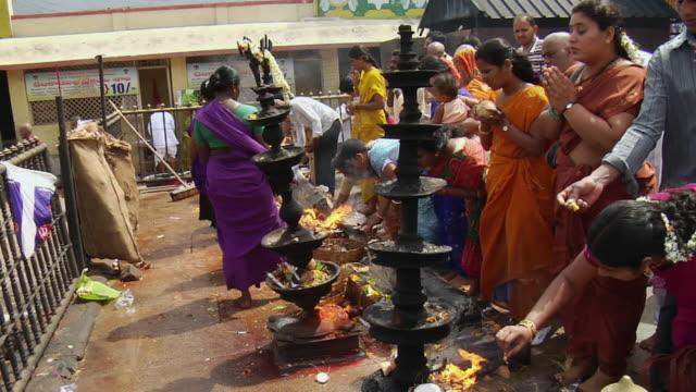 vídeos de stock e filmes b-roll de ms view of people offering prayers in temple / tirupati, andhra pradesh, india    - cara para baixo