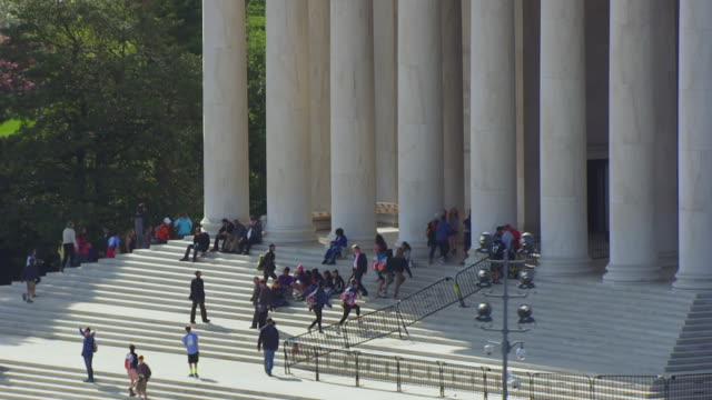 cu ts aerial pov view of people on steps of thomas jefferson memorial and pull out to reveal / tidal basin washington dc, united states  - jefferson memorial stock videos and b-roll footage