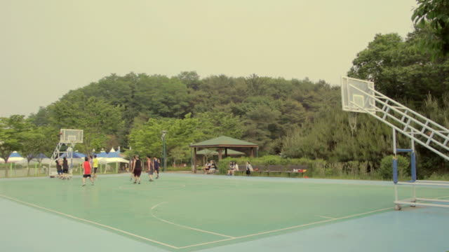 ws view of people playing basketball at park / ulsan, gyeongsangnam-do, south korea - コート点の映像素材/bロール