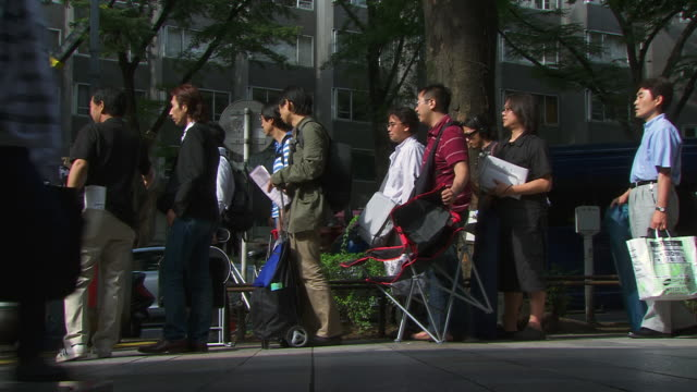 view of people queuing and walking for launch of iphone 3g at apple store with pedestrians passing / tokyo japan - 3g stock videos & royalty-free footage